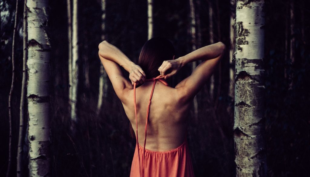woman-wearing-pink-halter-dress-standing-beside-grey-trees-231061